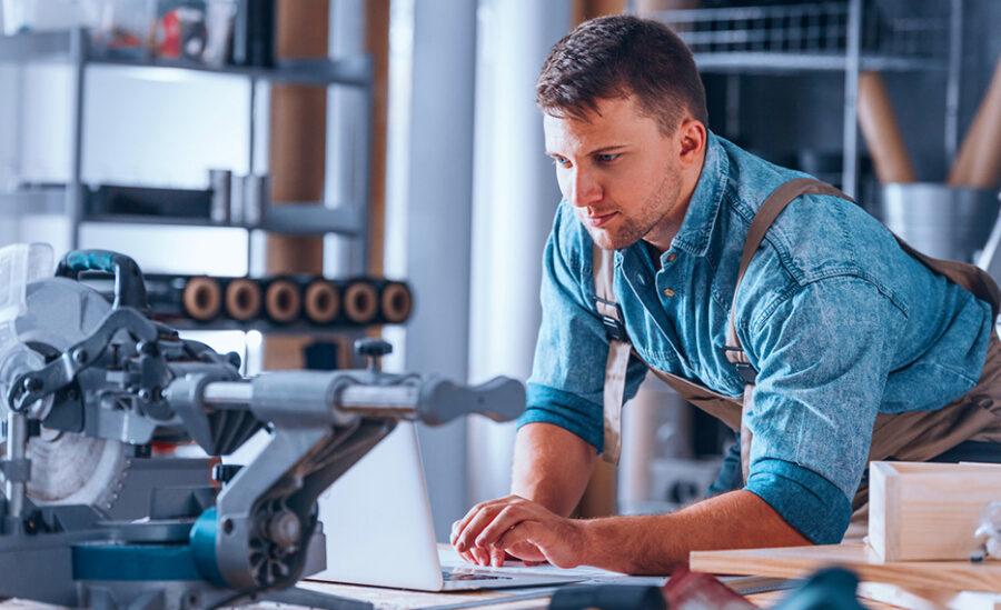 Рабочий на производстве смотрит в ноутбук