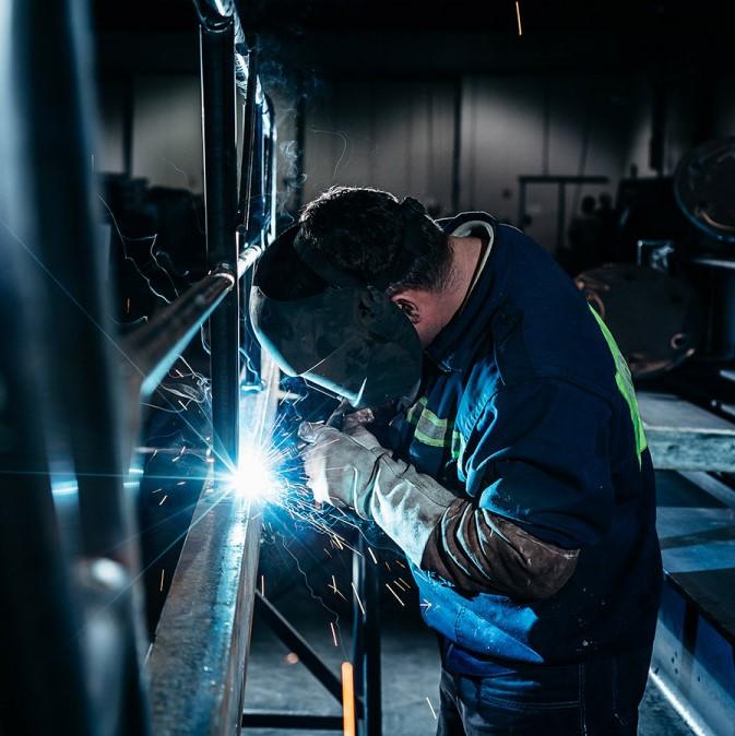 Сварщик в спецодежде работает с металлом, голубые искры